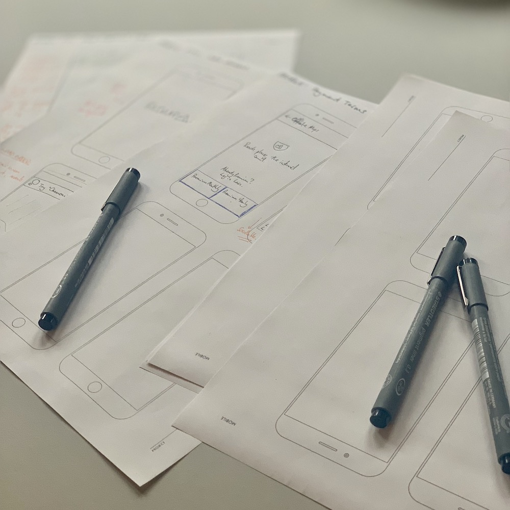 A photo of a stack of printed wireframe templates with sketches